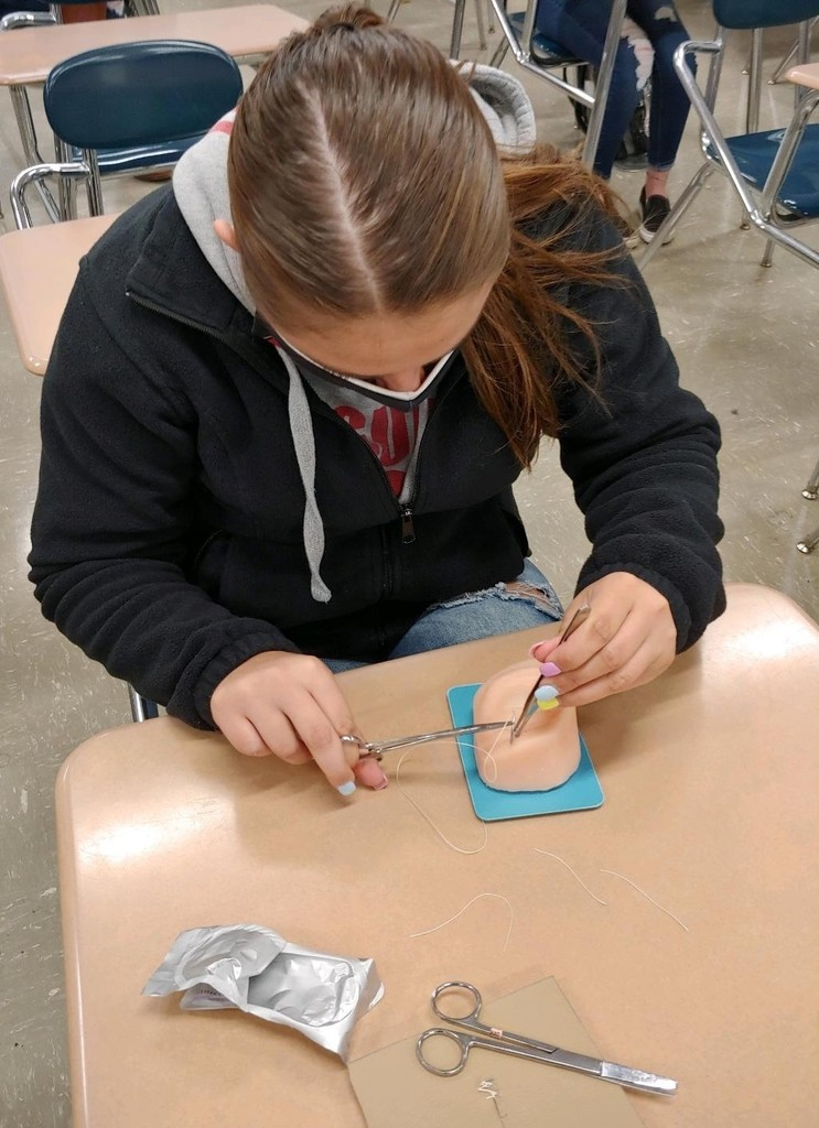 Teen girl focuses on suturing technique