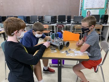 Three boys work on robots