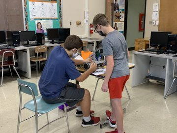 two boys work on their robot
