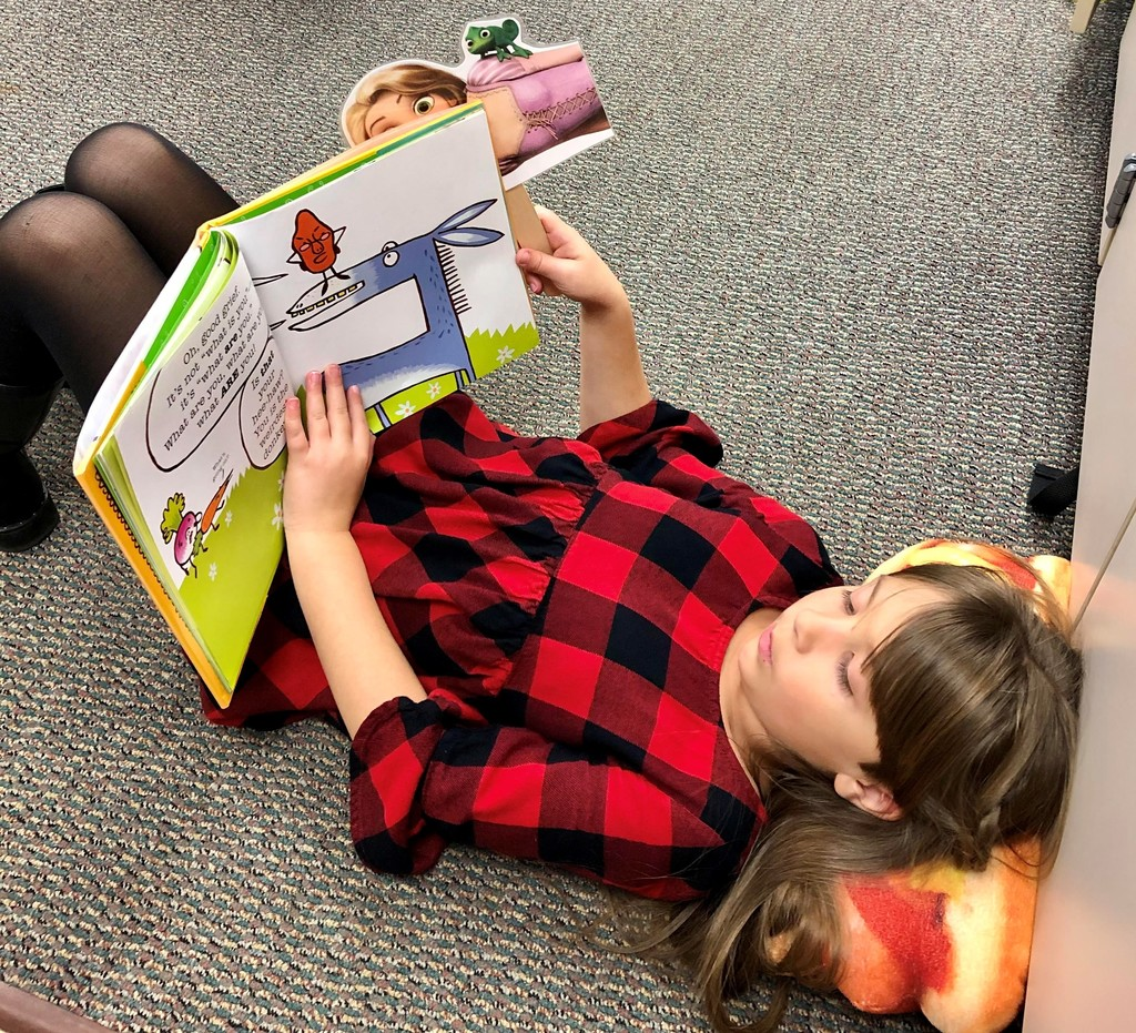 Girl lying on the floor reading a book