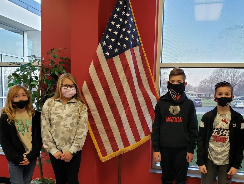 Two boys and two girls standing in front of a flag