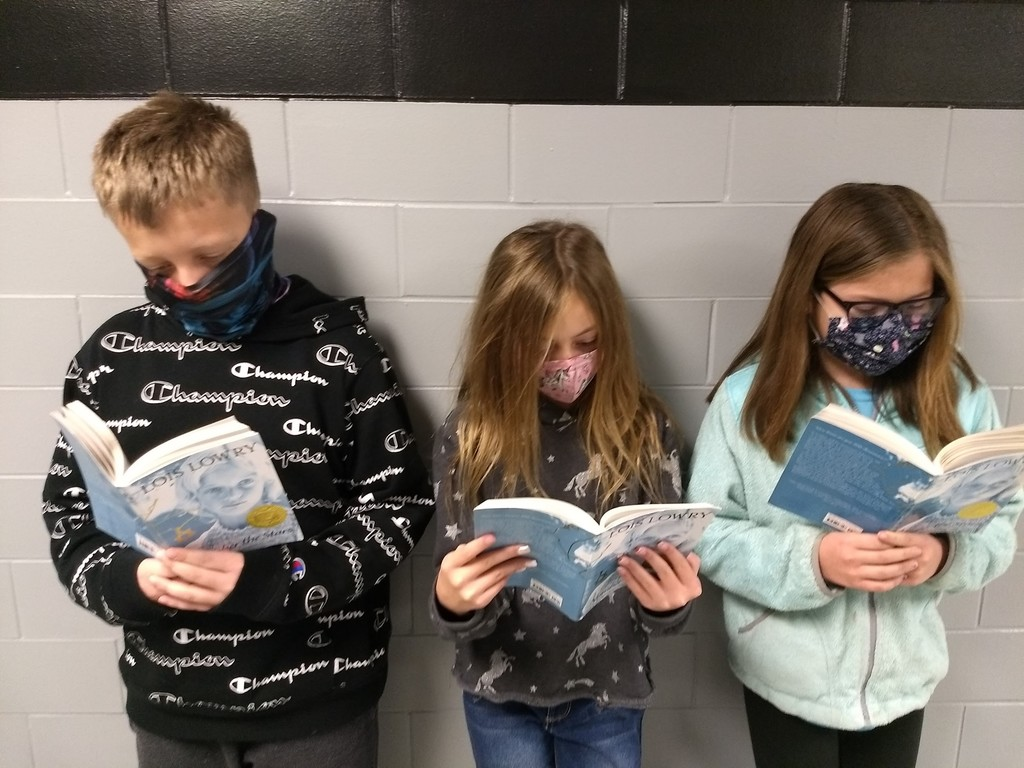 A boy and two girls stand in hall reading books