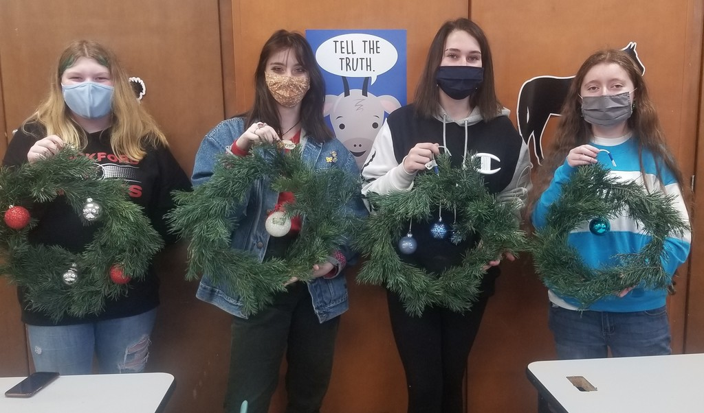4 girls holding Christmas wreaths they made