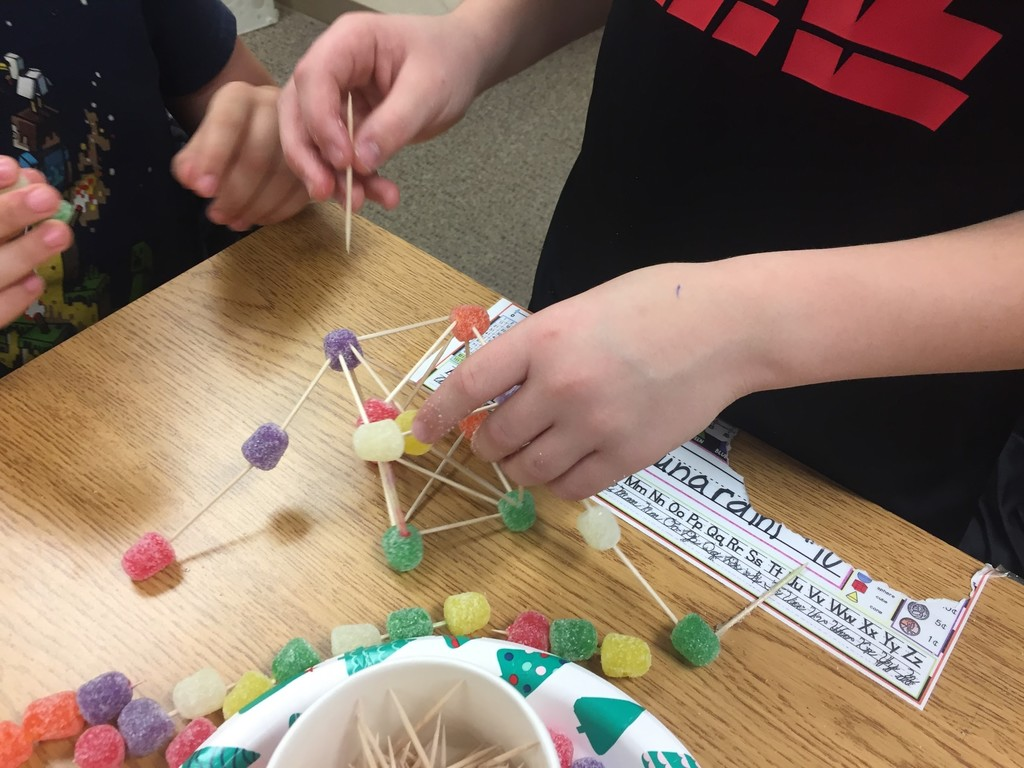 Student using tooth picks and gummies to build tower