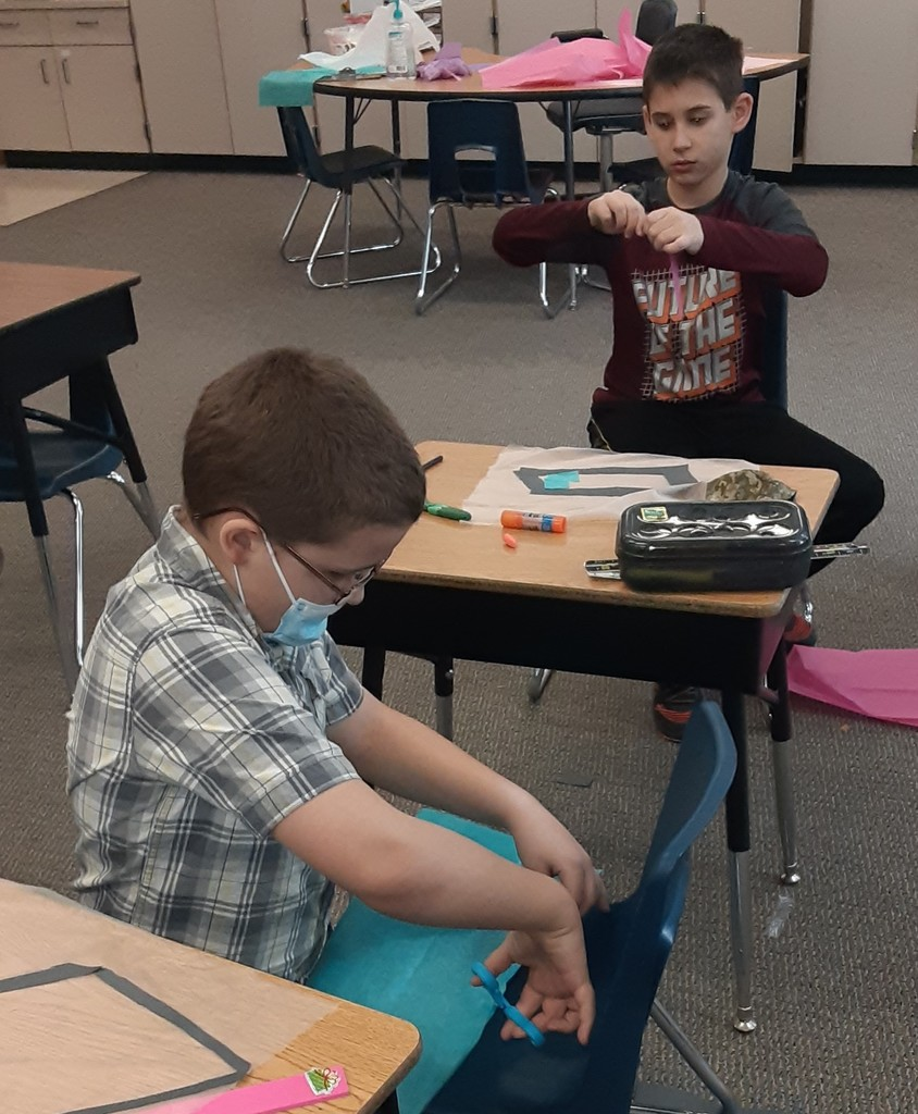 2 boys cutting out quadrilaterals