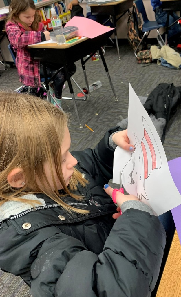2nd grade girl cuts out a picture of the Cat in the Hat