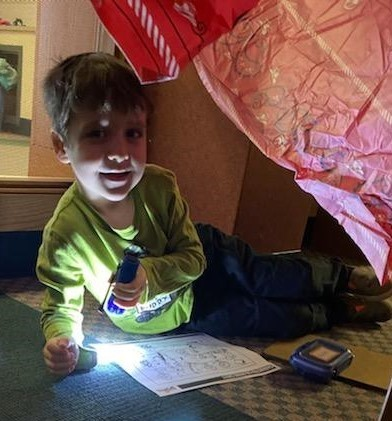 Young boy uses flashlight to work in a tent in library