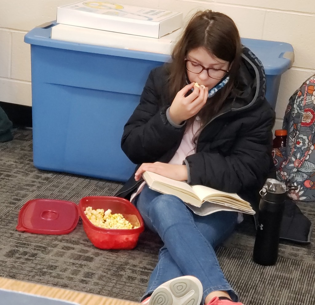 6th grade girl reads book while eating popcorn