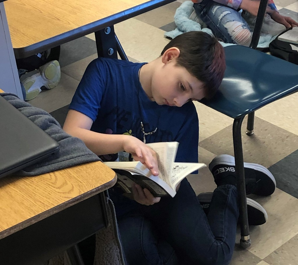 Boy sits on floor reading a book