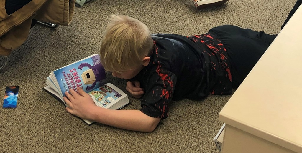 Boy lays on his tummy on the floor reading a book
