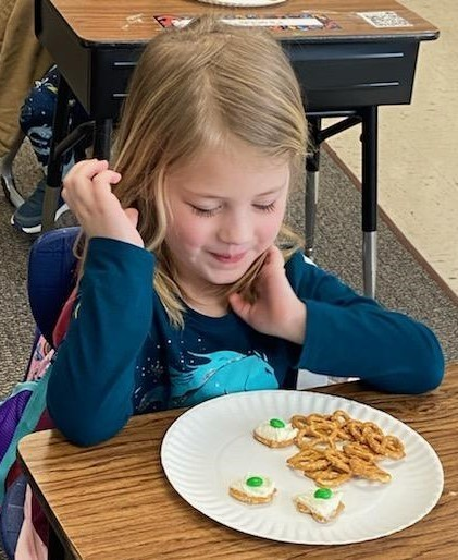 Preschool girl looks over her snack