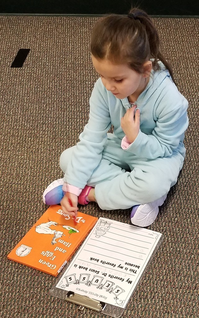 Girl sits on floor and answers questions about the book Green Eggs and Ham