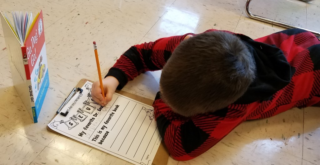 Kindergarten boy lays on floor doing his homework