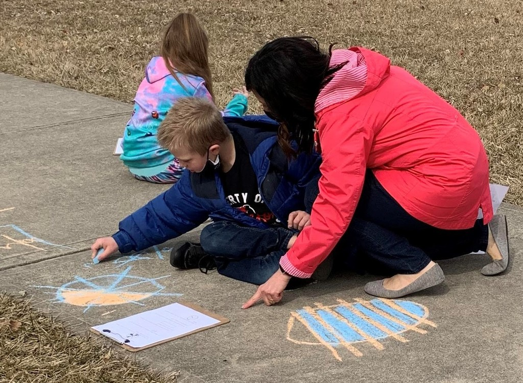 Mrs. Aulbach assists a student with an outdoor math problem