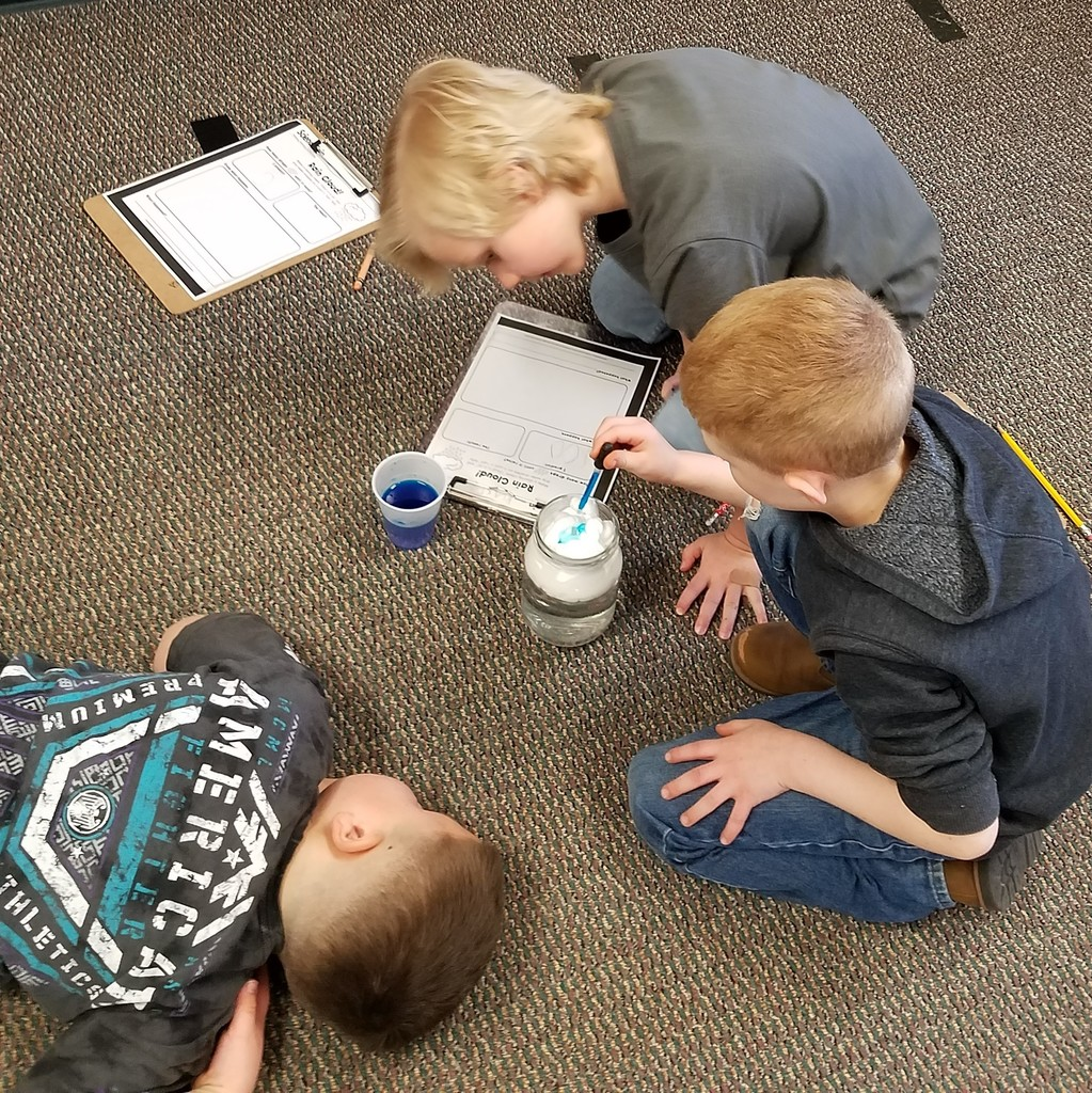3 kindergarten boys study their rain jar lesson
