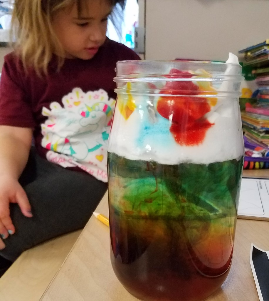 Kindergarten girl looks at rainbow rain jar