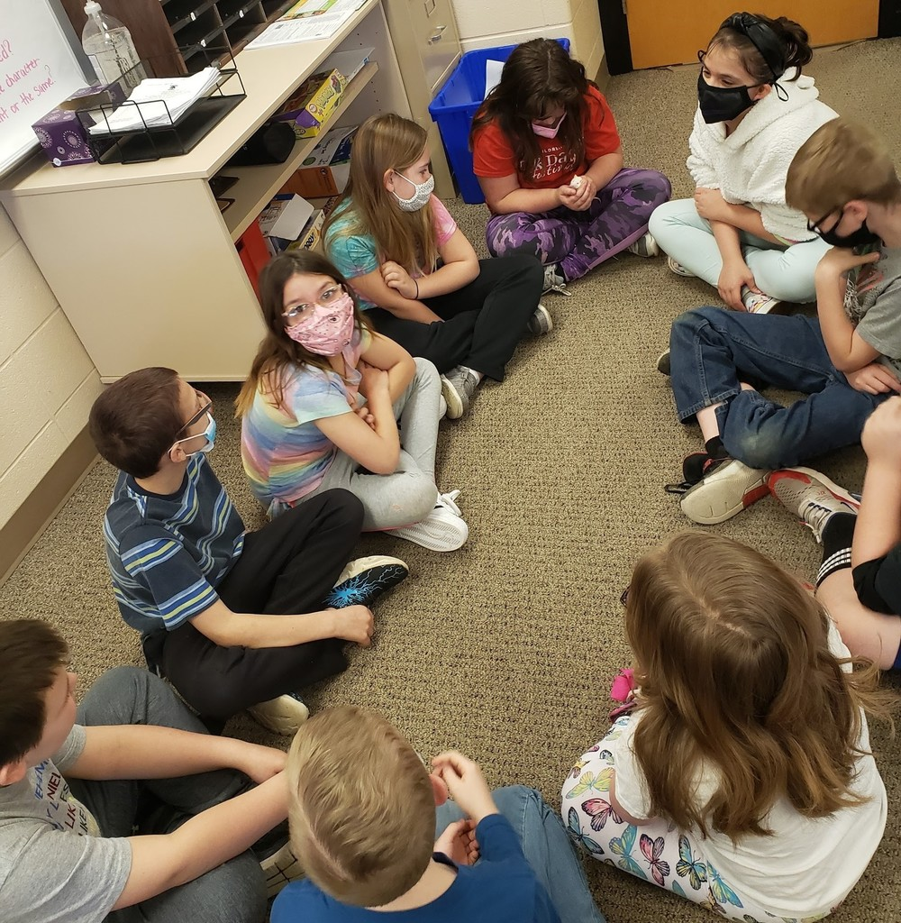 Group of masked 4th grade students sitting on floor petting a white rat