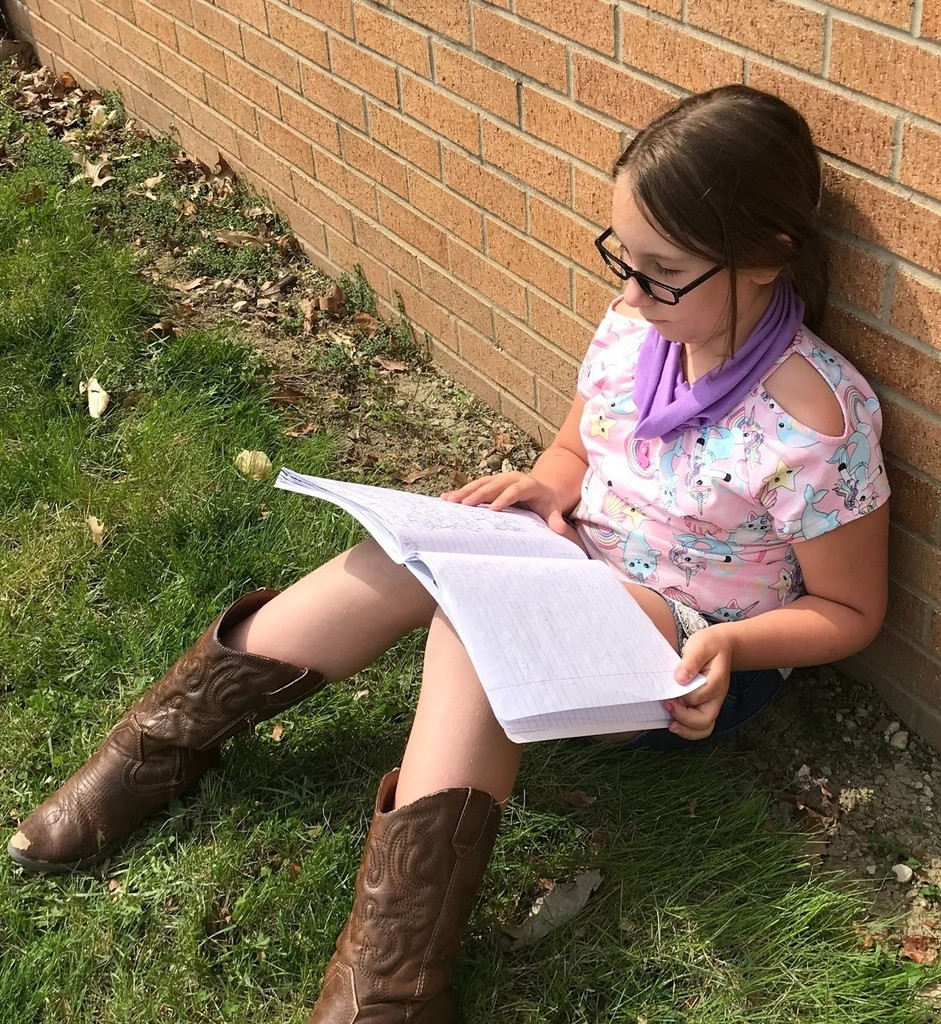 3rd grade girl working on assignment outdoors