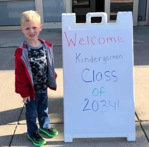 Kindergarten student standing in front of Class of 2034 sign