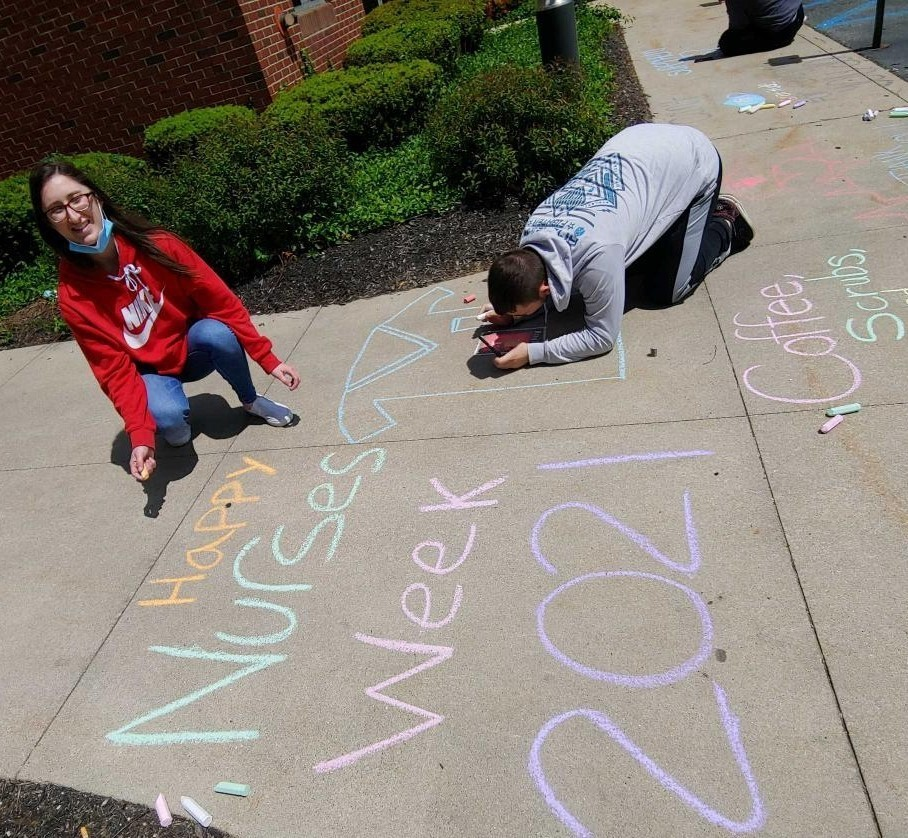 High school boy and girl work on chalk drawing