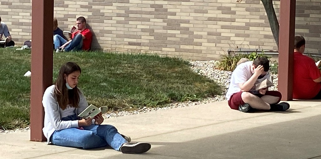 Students sitting outside reading at BJSHS