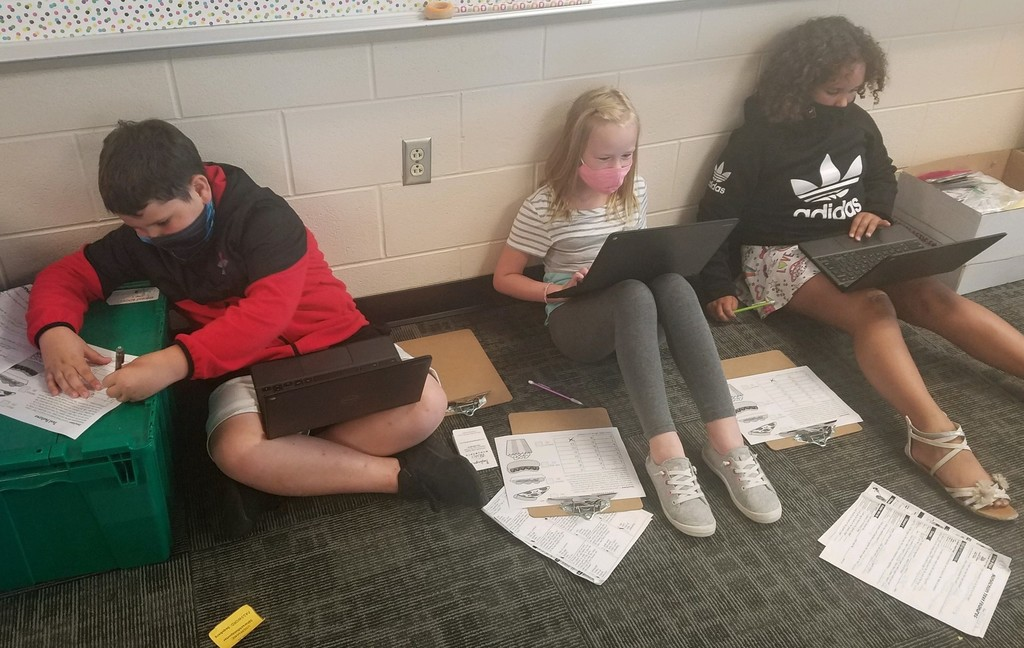 three students working on assignment on the floor
